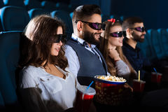 Cheerful friends together at the movie theatre royalty free stock image