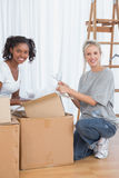 Cheerful friends unpacking boxes in new home Stock Photo