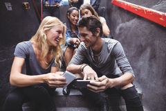 Cheerful friends using mobile phones on steps at nightclub Stock Photos