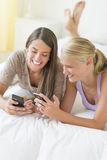 Cheerful Friends Using Smart Phones In Bed Stock Photos