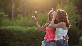 Cheerful friends walking in the park. Cheerful friends walking in a summer park. The girl shows the index finger to the side. Girls having fun talking to each stock video footage