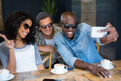 Cheerful friends wearing sunglasses while taking selfie in coffee shop Royalty Free Stock Image
