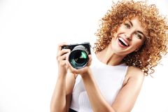 Cheerful frizzy-haired lady holding a digital camera. Cheerful frizzy-haired woman holding a digital camera royalty free stock photos
