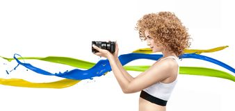 Cheerful frizzy-haired lady holding a long-focus lens. Cheerful frizzy-haired woman holding a long-focus lens royalty free stock images