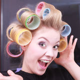 Cheerful funny blond girl hair curlers rollers by haidresser in beauty salon. Portrait of funny happy woman in beauty salon. Cheerful blond girl with hair Royalty Free Stock Photos