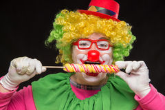 Cheerful funny clown in a hat with a big candy Stock Image