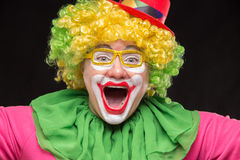 Cheerful funny clown in a hat with a big candy Stock Photos