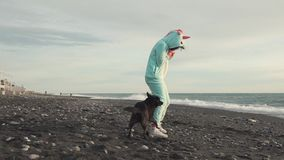 A cheerful lady in a kigurumi costume is having good time by the sea with a dog. Cheerful and funny lady in a kigurumi costume plays with a playful dog by the stock video footage