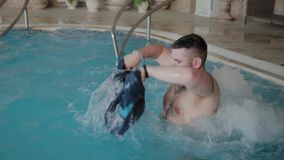 Cheerful funny man bathes in the pool jacuzzi and washes his shorts. stock footage