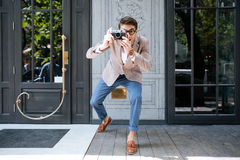 Cheerful funny photographer in round glasses taking pictures on street. Cheerful funny man in round glasses standing and taking pictures on the street of the stock photography