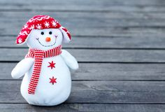 Cheerful and funny snowman in a red hat and red scarf on a gray wooden background. Close-up. copyspace stock photo