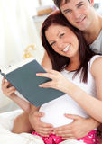 Cheerful future parents reading a book Royalty Free Stock Photos