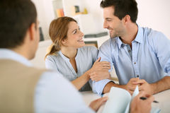 Cheerful future property owners. Young couple meeting construction planner Royalty Free Stock Photos