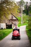 Cheerful gardener riding tractor mower. Cheerful gardener speedy riding tractor mower on countryside road. Shallow DOF, tractor front and man?s face in focus Stock Photos