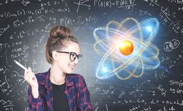 Cheerful geek girl looking at atom model hologram royalty free stock images