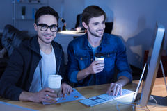 Cheerful genius hackers celebrating their success. Now we are rich. Cheerful genius handsome hackers having coffee and smiling while being happy about their Royalty Free Stock Photo