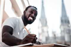 Cheerful gentleman smiling while taking some notes outdoors. Dreaming and writing it down. Selective focus on a hand of an African American man smiling Stock Photography