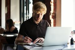 Cheerful ginger caucasian man using computer and smartphone sitting in cafe having coffee. Concept of young business people stock images