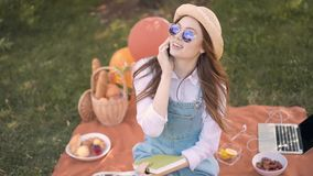Cheerful ginger college student in straw hat and sunglasses talking on phone in park stock video footage