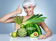 Cheerful girl with an abundance of fruits and vegetables. Stock Photos