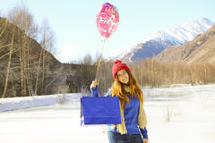 Cheerful girl with a balloon and a package Royalty Free Stock Photo