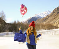 Cheerful girl with a balloon and a package with a gift Royalty Free Stock Images