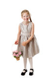 Cheerful girl with a basket of artificial flowers Royalty Free Stock Photos