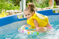 Cheerful girl bathing trying to get into the swimming circle Royalty Free Stock Photos