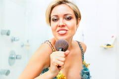 Cheerful girl in bathroom singing in fluffy brush Royalty Free Stock Photos