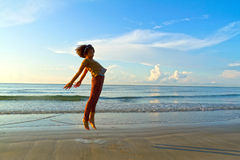Cheerful girl on the beach at dawn Stock Images