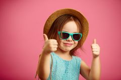Cheerful girl in beach hat and sunglasses, shows thumbs up, has a good mood, stands on isolated pink background. stock images