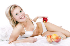 Bed of a beautiful blond woman holding apple. Royalty Free Stock Photo