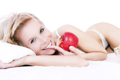 Bed of a beautiful blond woman holding apple. Royalty Free Stock Image