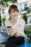 Cheerful Girl at the Bench Holding Mobile Phone Royalty Free Stock Photography