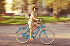 Cheerful girl on a bicycle. In movement Royalty Free Stock Photography