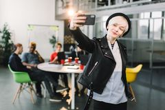 Cheerful girl in black hat and leather jacket making video call via smartphone. Young woman waving hand and smiling at royalty free stock photo
