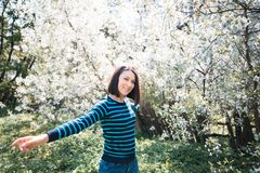 Cheerful girl in blooming garden. Spring mood. Sunny young woman Stock Photos