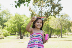 Cheerful girl blowing soap bubbles at park Royalty Free Stock Photography