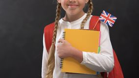 Cheerful girl with books and British flag smiling at camera, language studying. Stock footage stock video