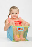 Cheerful girl in a box for toys Stock Image