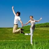 Cheerful girl and boy are jumping. On grass Royalty Free Stock Photography