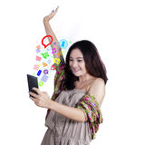 Cheerful girl browsing internet on cellphone. Happy teenage girl with casual clothes using cellphone to use social media, shot in the studio Stock Image