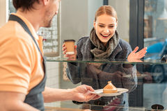 Cheerful girl buying sweets and coffee in shop Stock Photography