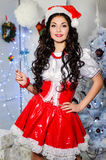 Cheerful girl with candy in the Santa Claus hat. New Year decora. Tions, gifts, Christmas tree Royalty Free Stock Image