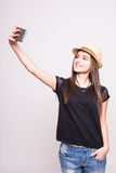 Cheerful girl in cap making selfie on smartphone on grey Stock Photo