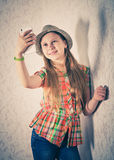 Cheerful girl in cap and making selfie on smartphone. Stock Image