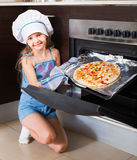 Cheerful girl in cap prepared Italian pizza. At home Royalty Free Stock Photo