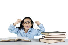 Cheerful girl celebrating her success with books. Portrait of cheerful girl celebrating her success while sitting in front of her books on table, isolated on royalty free stock photography