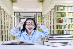 Cheerful girl celebrating her success in library Royalty Free Stock Photos