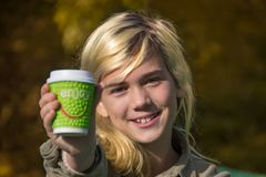 Cheerful girl. Holds a coffee Cup with the inscription `Enjoy Stock Image